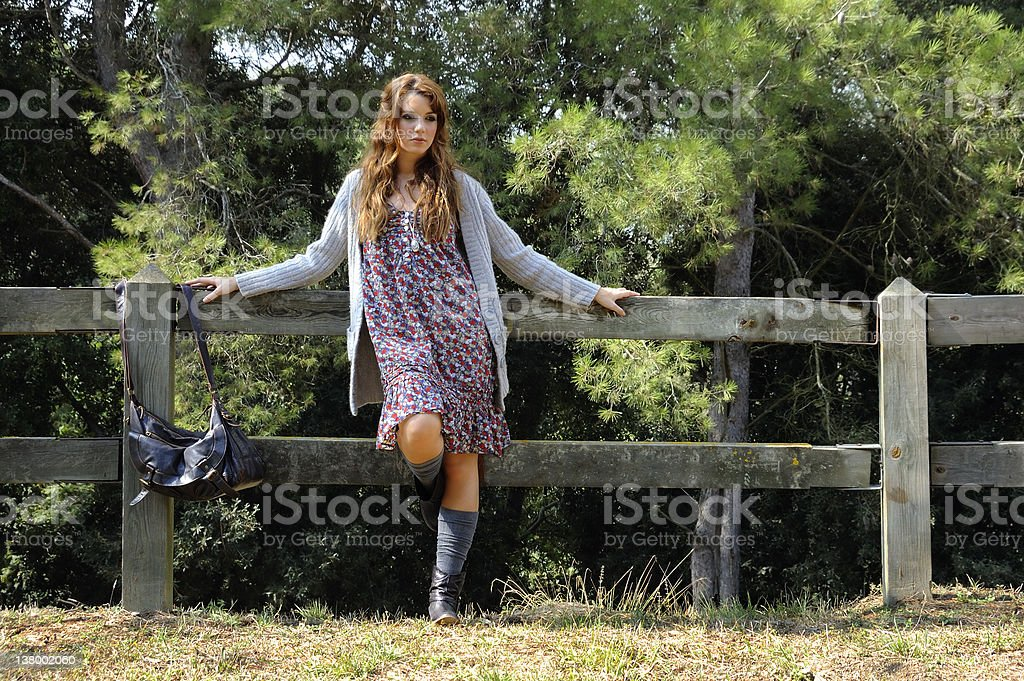 Girl supported in a wood fence royalty-free stock photo