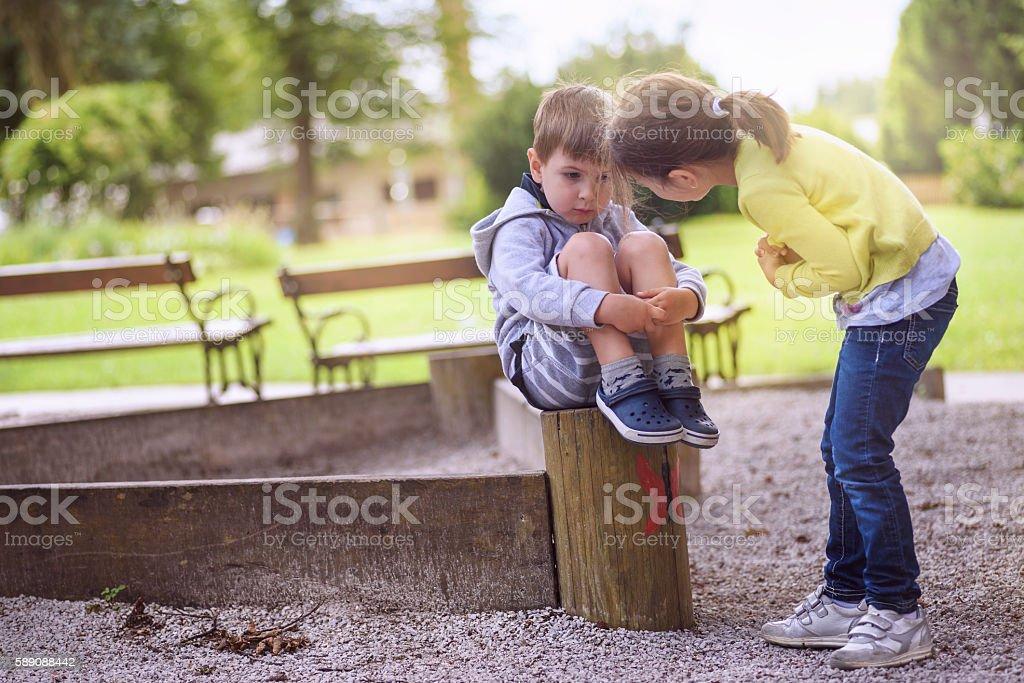 Girl Supporting Sad Boy Sitting Alone stock photo