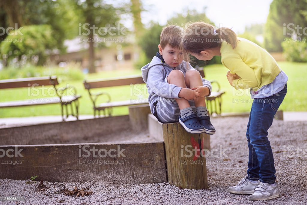 Girl Supporting Sad Boy Sitting Alone stock photo