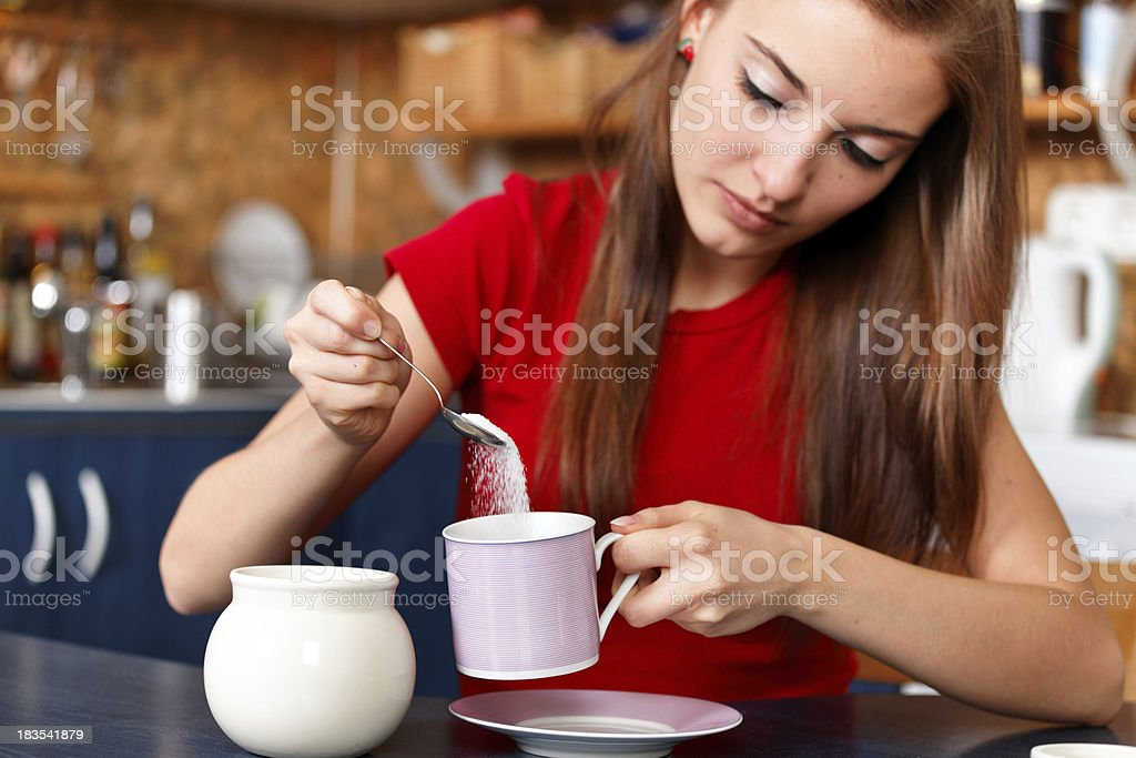girl sweetening her tea or coffee stock photo