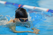 girl swimming butterfly stroke style in the blue water pool.