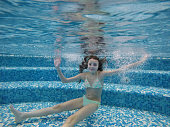 Girl swimming under water in the pool