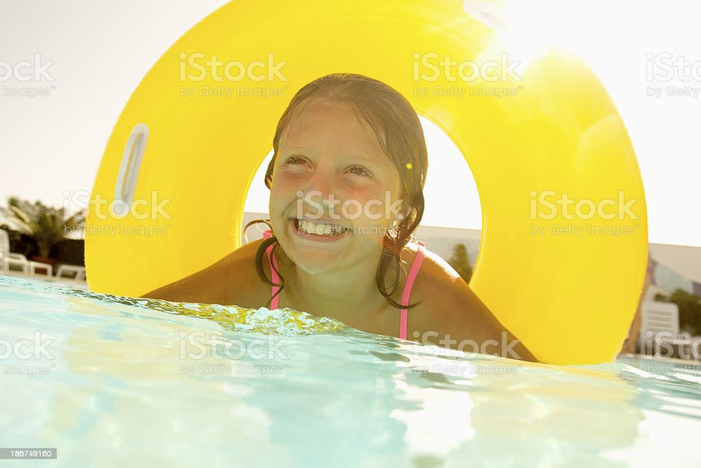 Girl Swimming With Yellow Tube royalty-free stock photo