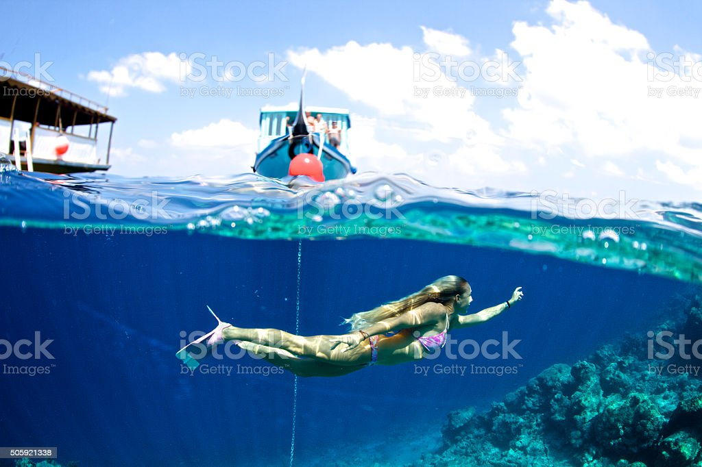 Girl swims beneath the surface of the ocean stock photo