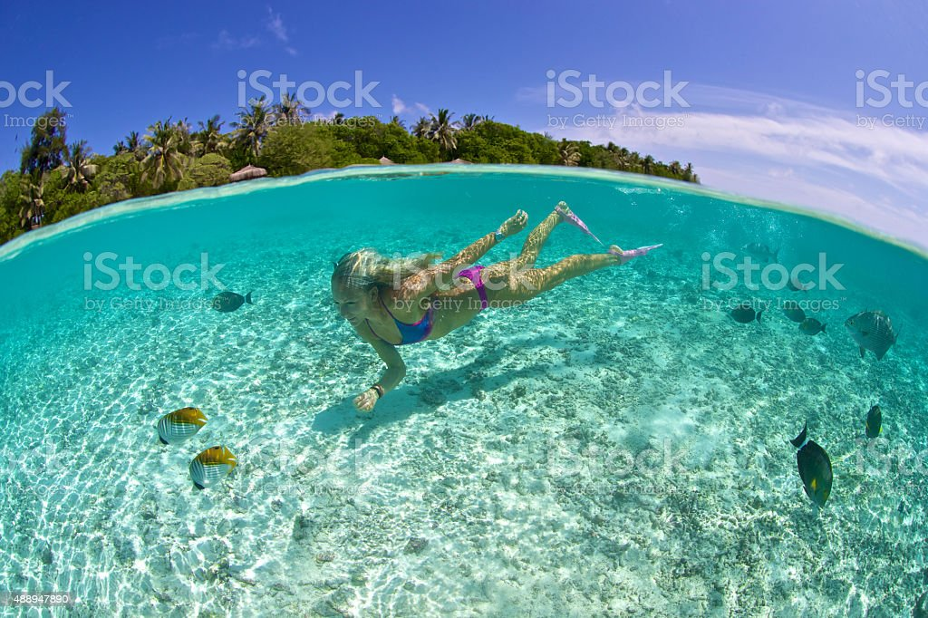 Girl swims in tropical lagoon with fish and resort stock photo