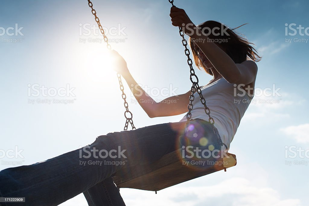 Girl Swinging Against Sun and Blue Sky royalty-free stock photo