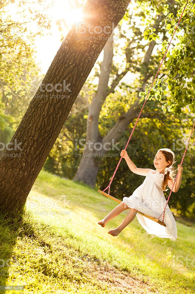 Girl Swinging In Park stock photo