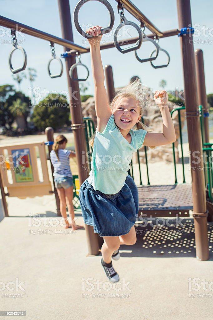 Girl swinging on jungle gym stock photo