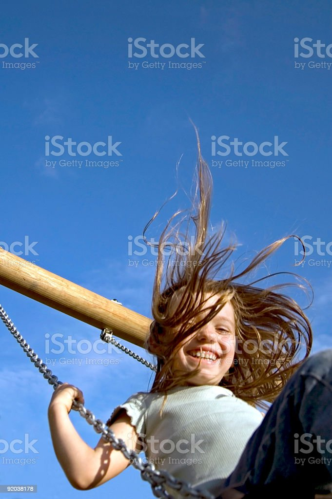 Girl swinging with a big smile royalty-free stock photo