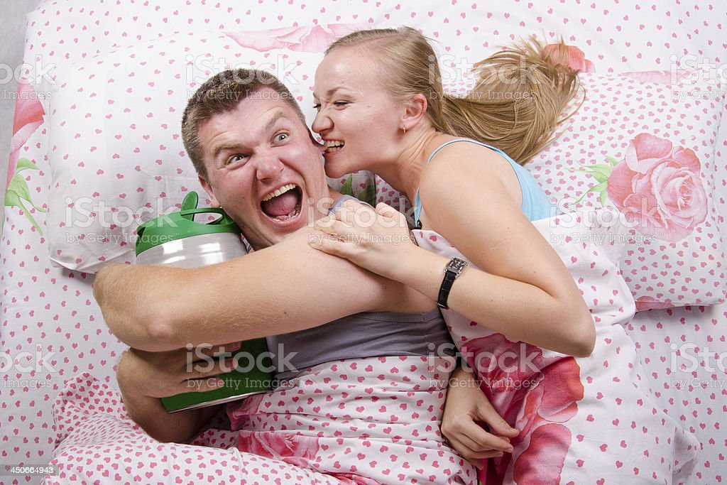 girl takes guy keg of beer while lying in bed royalty-free stock photo