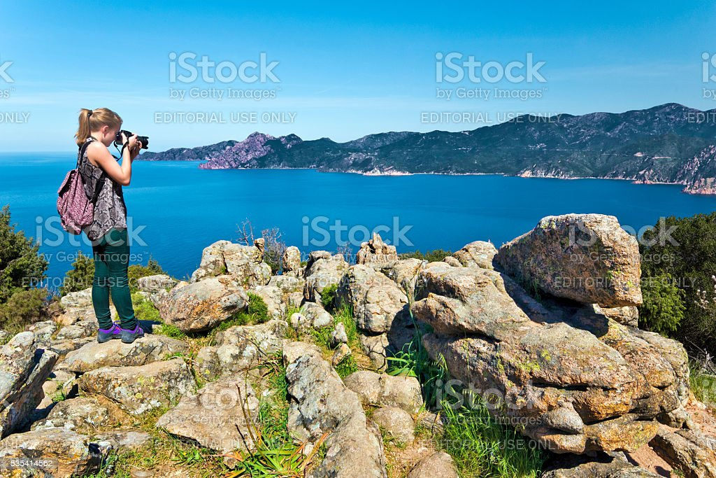Girl takes picture of Bay Porto in Corsica Island stock photo