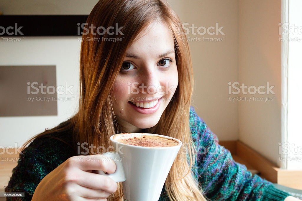 Girl taking a cup of coffee stock photo