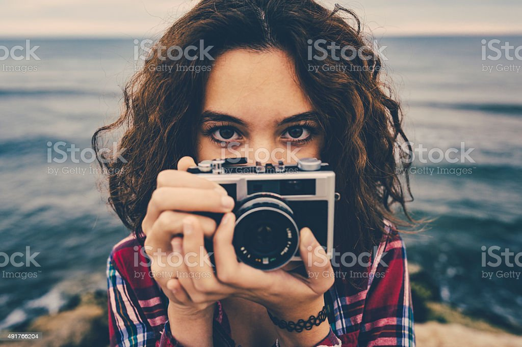 Girl taking a photo at sea with a film camera royalty-free stock photo
