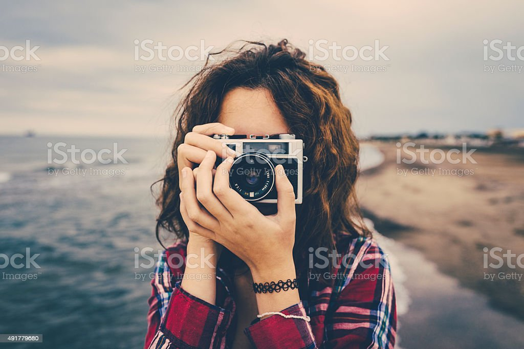 Girl taking a photo at sea with a film camera stock photo
