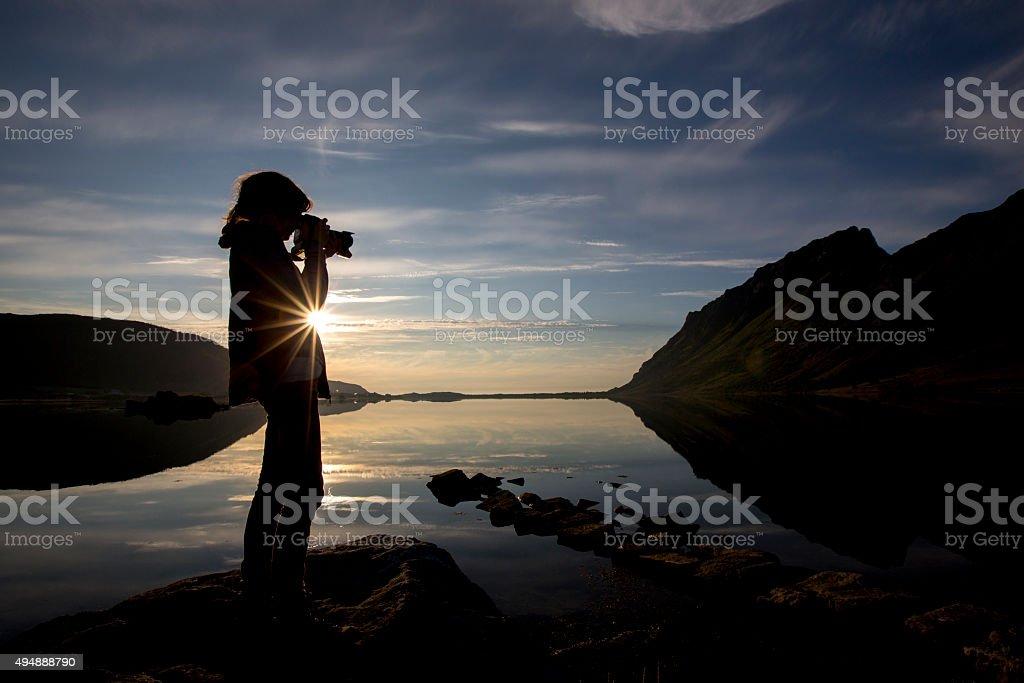 girl taking a photo from midnight sun,lofoten,norway stock photo