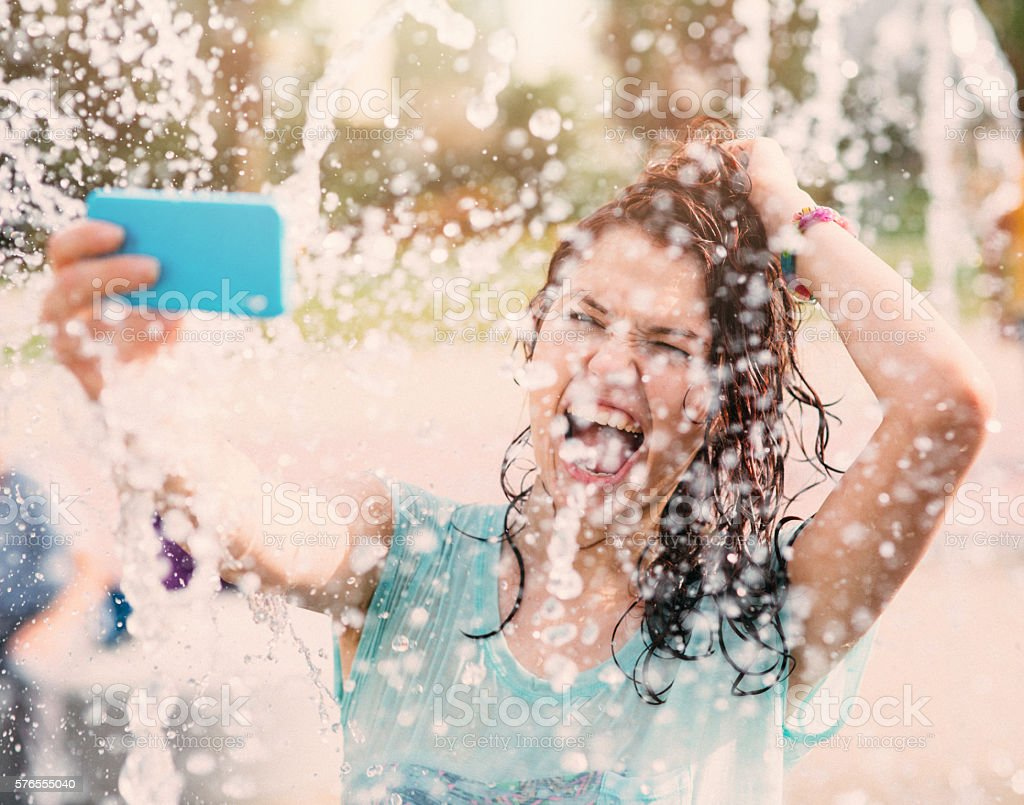 Girl taking a selfie under a fountain stock photo