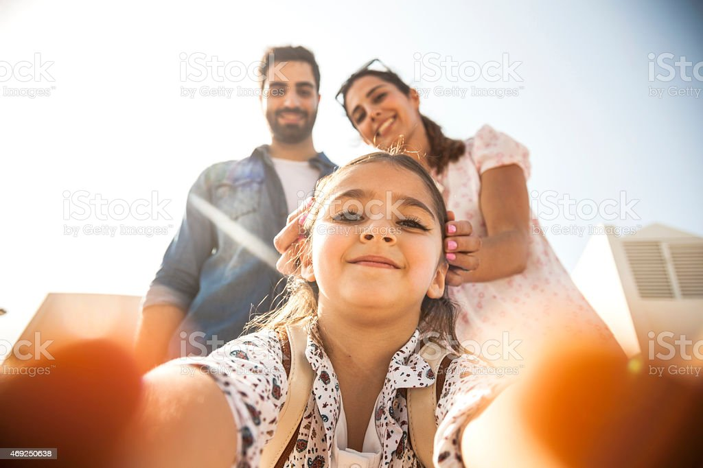 Girl taking a selfie with parents stock photo