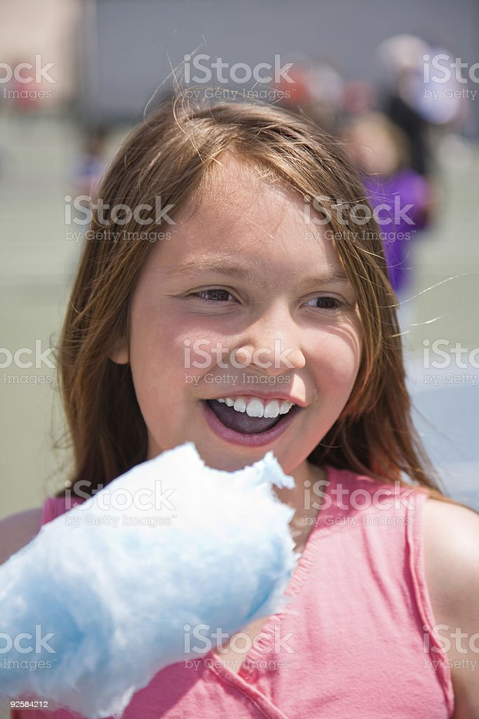 Girl taking bite of cotton candy royalty-free stock photo