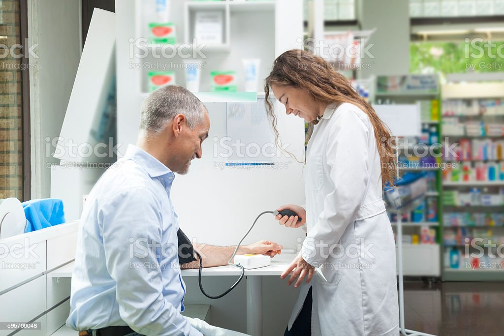 Girl taking blood pressure to mature man stock photo