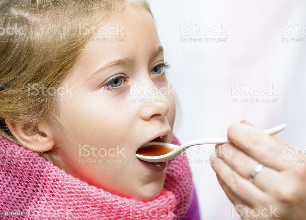 Girl taking medicine from a spoon. stock photo