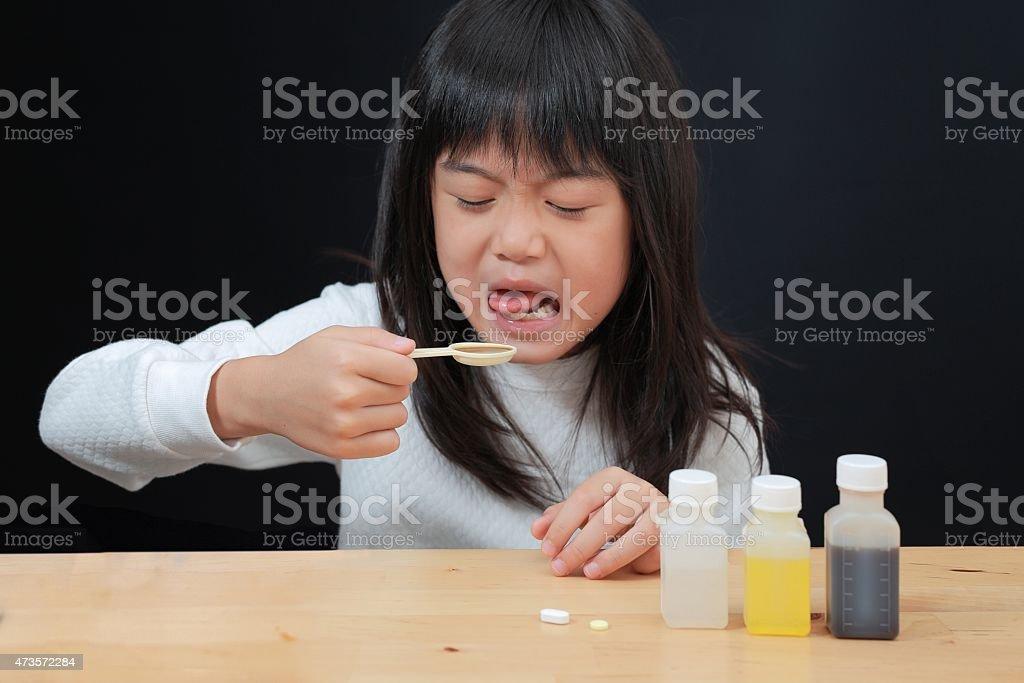 girl taking medicine stock photo