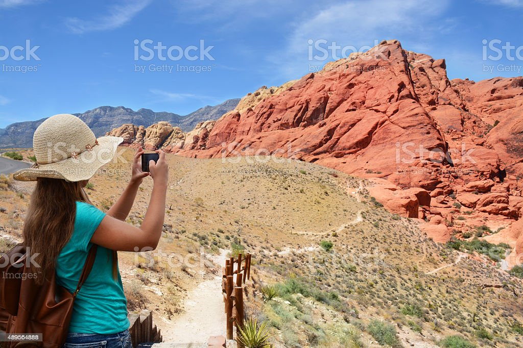 Girl taking photo with her smartphone on hiking trip. stock photo