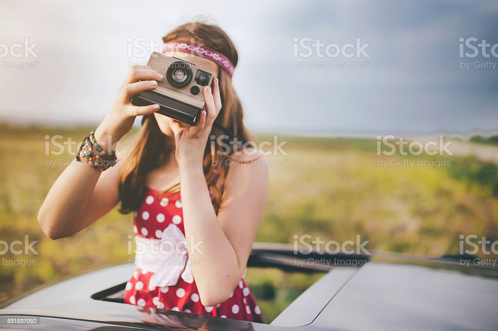 Girl taking photo with instant camera throught car sunroof stock photo