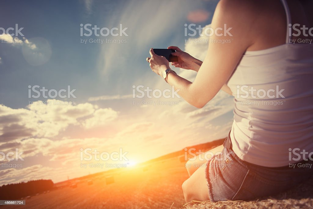 Girl taking photo with mobile phone at sunset outdoors stock photo