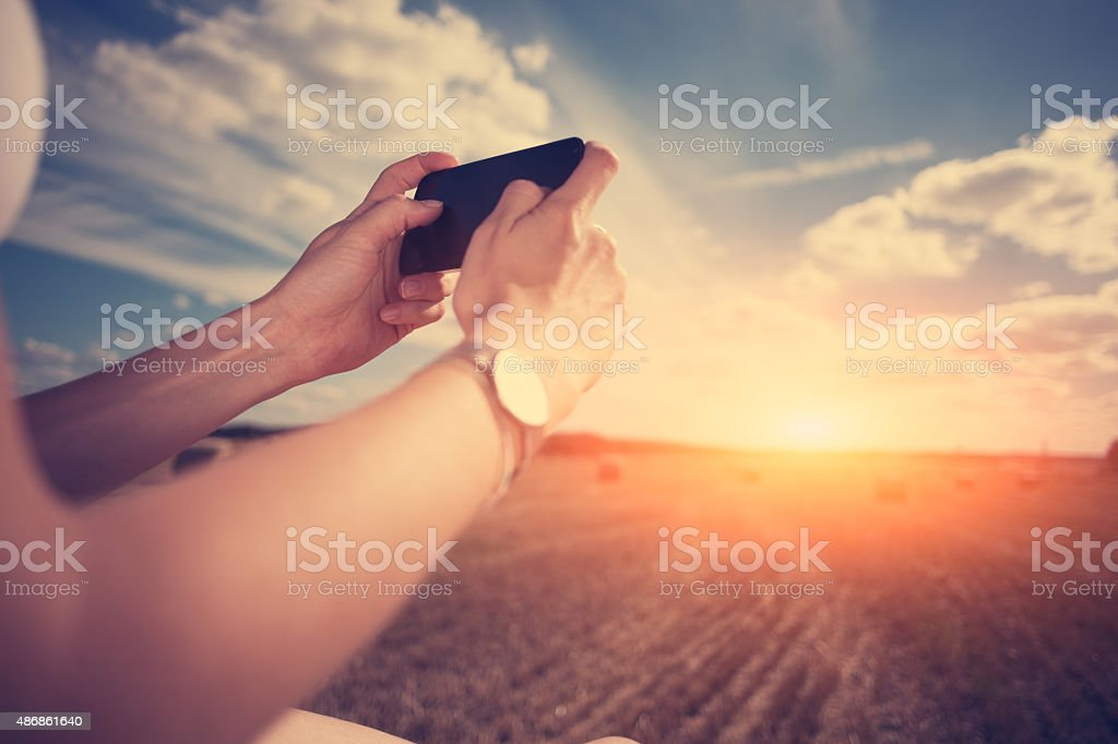 Girl taking photo with mobile phone in the field stock photo