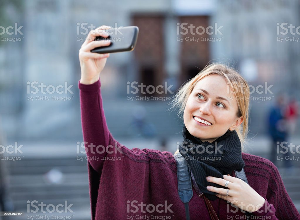 Girl taking picture with her phone in the town stock photo