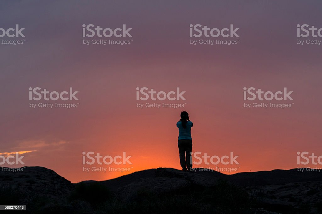girl taking pictures of sunset at hill top stock photo