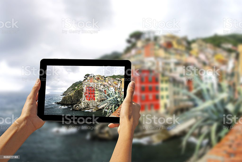 Girl taking pictures on a tablet in Riomaggiore stock photo