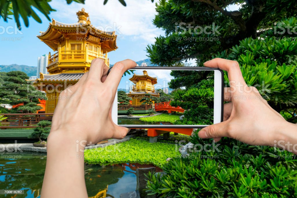 Girl taking pictures on mobile smart phone in Front View The Golden Pavilion Temple in Nan Lian Garden stock photo