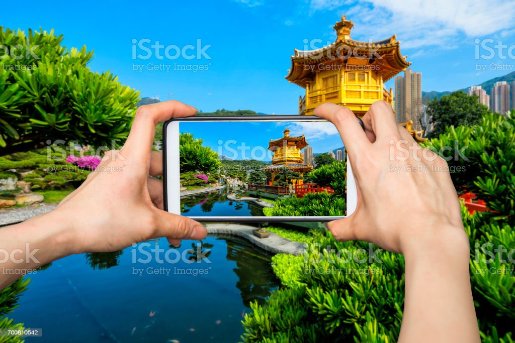Girl taking pictures on mobile smart phone in Jiuzhaigou National Park,China stock photo