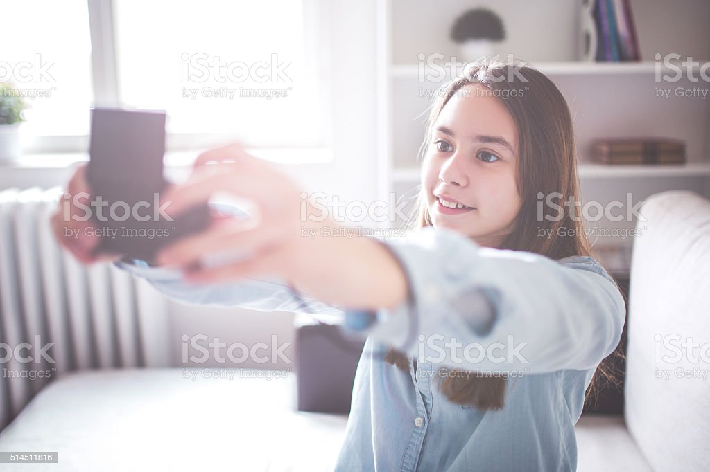 Girl taking selfie at home stock photo