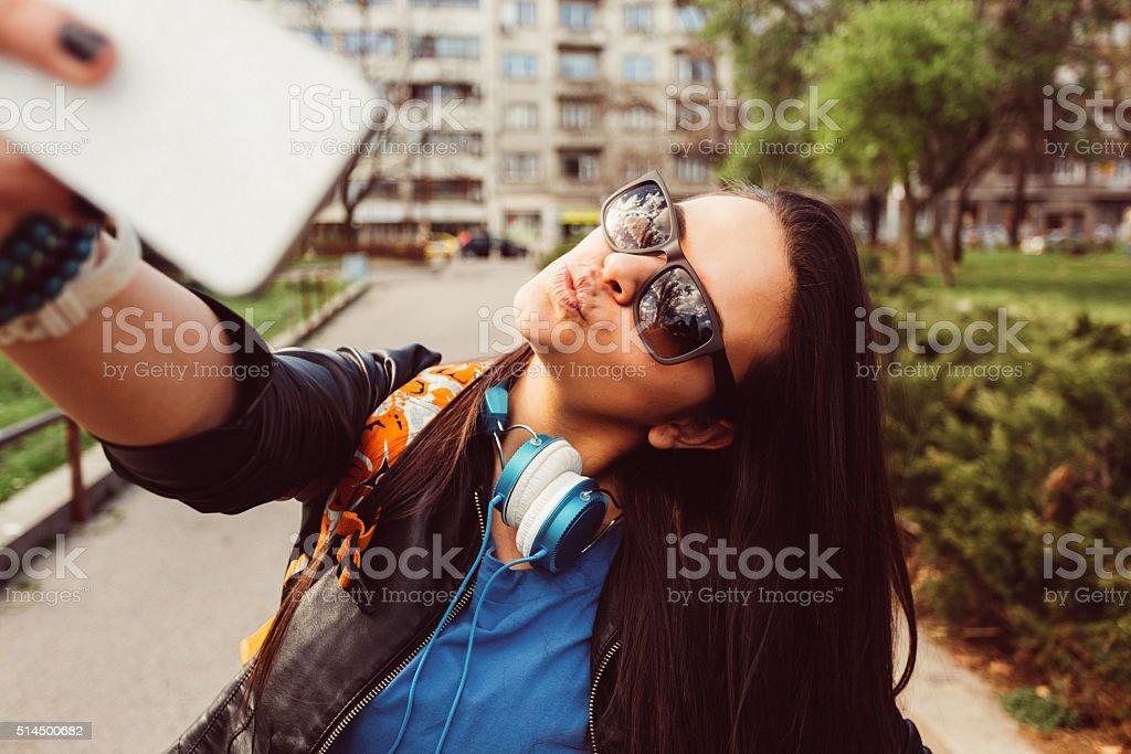 Girl taking selfie in the city stock photo