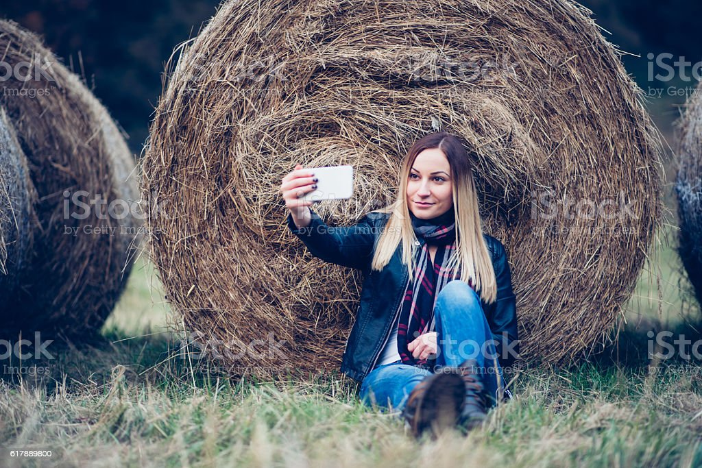 Girl taking selfie in the field stock photo