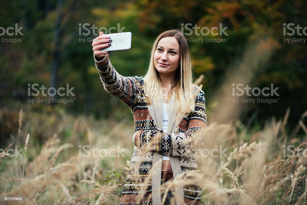 Girl taking selfie in the field stock photo