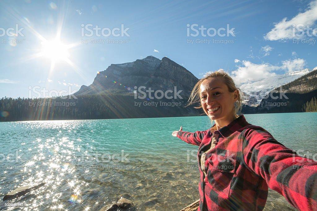 Girl taking selfie portrait by mountain lake stock photo