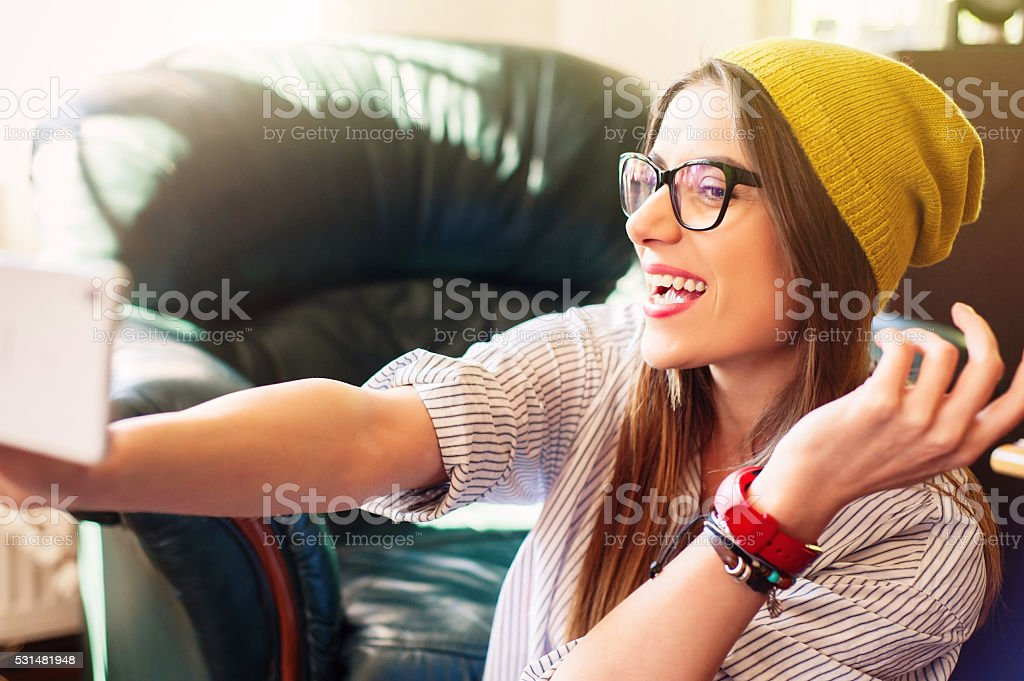 Girl taking self-portrait and laughing. stock photo