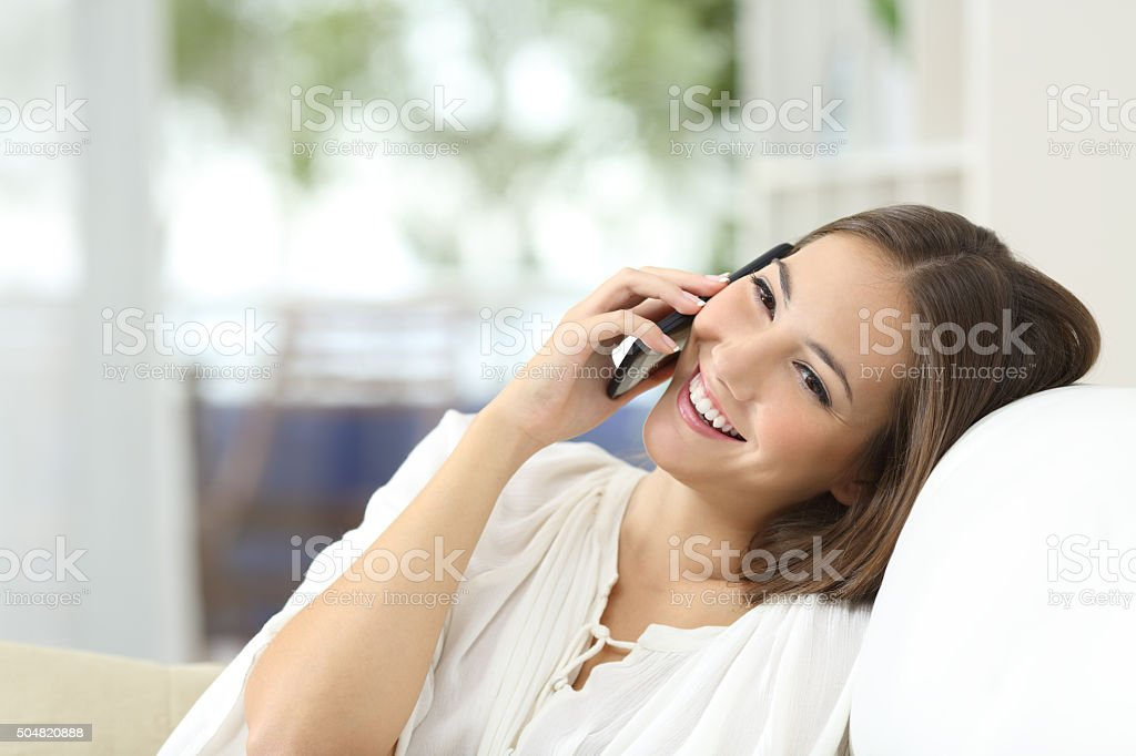 Girl talking on the mobile phone at home stock photo
