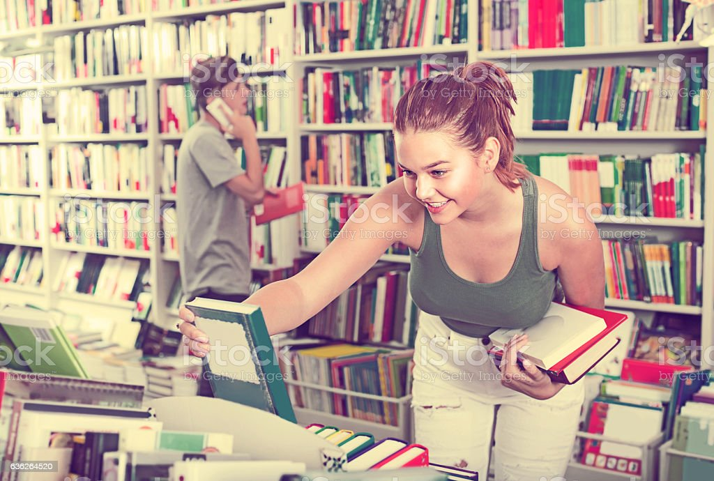 girl teenager choosing book in shop stock photo