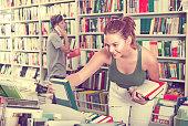 girl teenager choosing book in shop