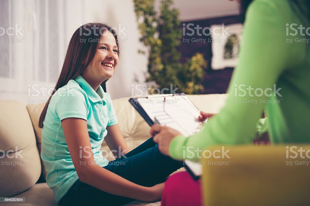 Girl teenager is happy after a successful therapy by psychologists stock photo