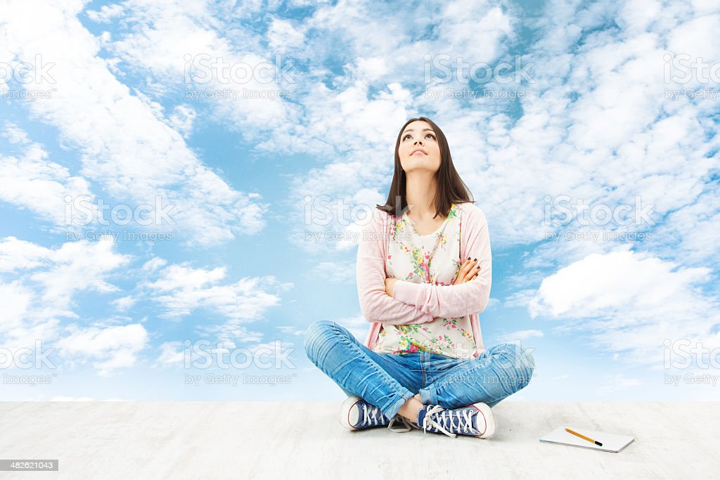 Girl teenager thinking inspiration or planning idea, blue sky stock photo