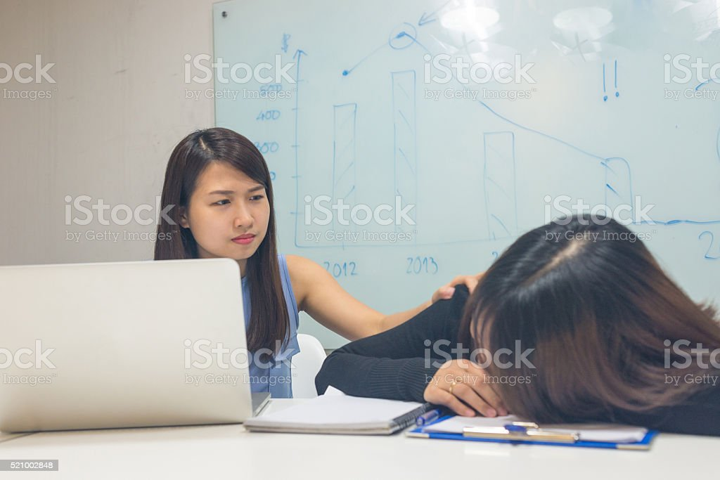 Girl telling languid colleague to go home for a rest stock photo