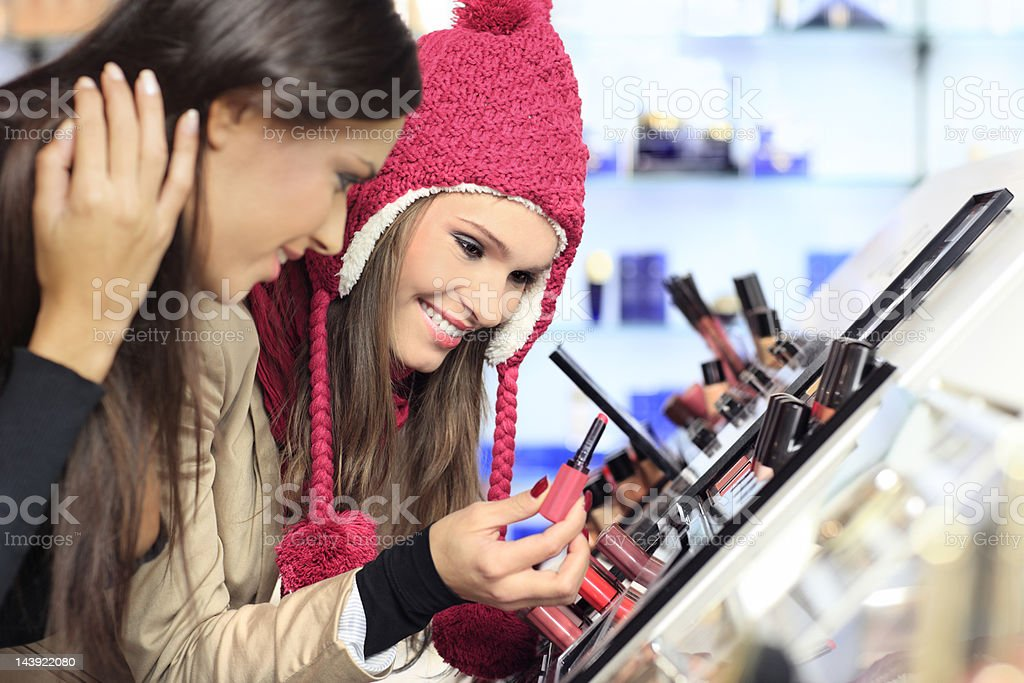 Girl testing and  purchases cosmetics in the beauty shop stock photo