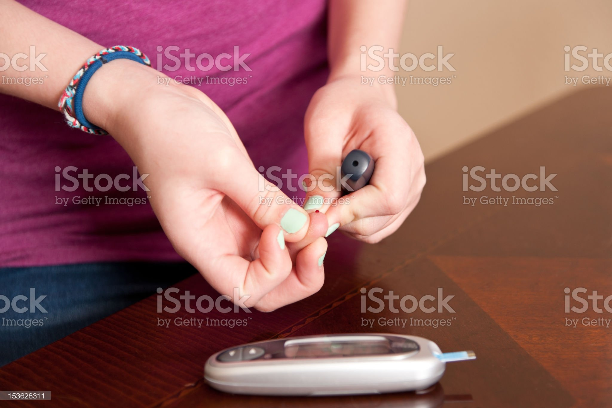 Girl testing her blood glucose level royalty-free stock photo