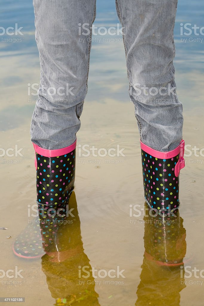 Girl tests her polka dot galoshes in shallow water royalty-free stock photo