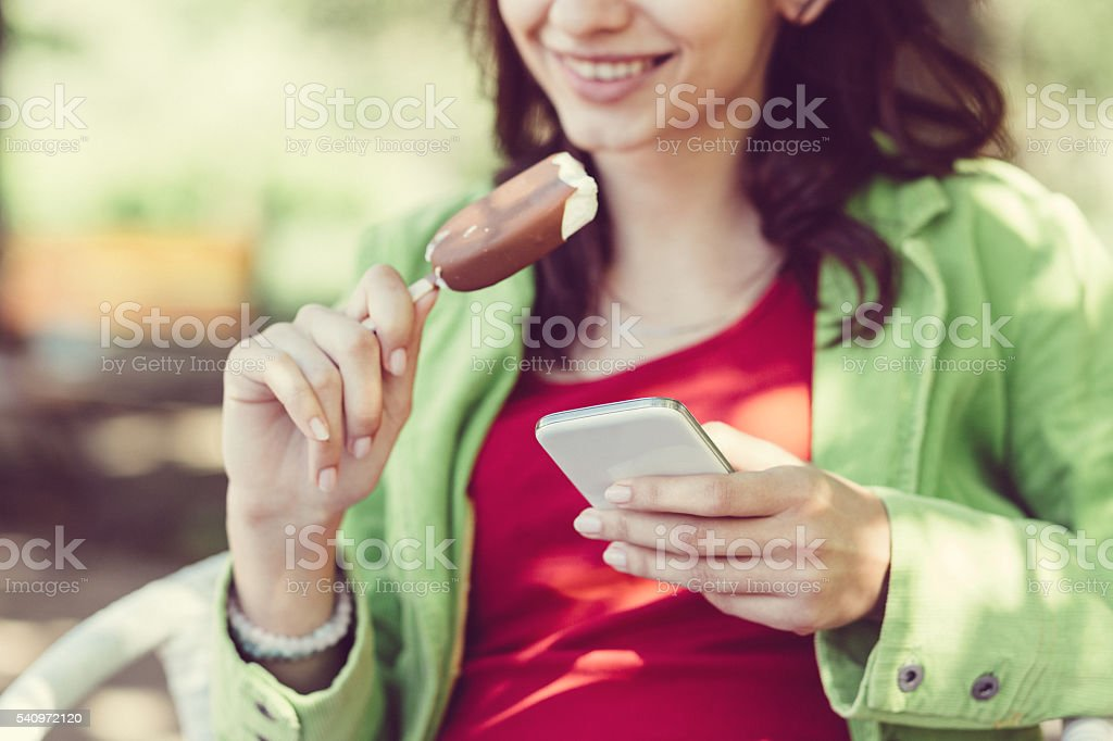 Girl texting and eating ice-cream stock photo